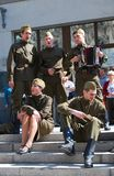 Young actors sing songs on the street. Young actors dressed as soldiers perform on Kamergersky lane in Moscow city center. They sing war songs, one of them play Royalty Free Stock Photos