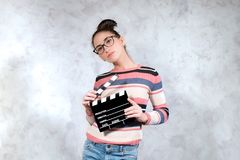 Young actress audition posing with movie clapper board. Young woman actress serious face expression posing with movie clapper board stock images