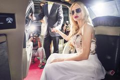 Young actress getting out of the car to attend the premiere. Attending the red carpet event by stepping out of the limousine at the night of the premiere Royalty Free Stock Images