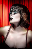 Young actress with venetian mask over cabaret background Stock Photo