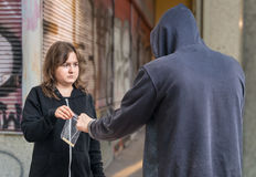 Young addicted woman is buying drugs from drug dealer Stock Photos