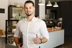 Young administrator standing with at cafe, showing thumbs up. Young male administrator standing with at cafe, showing thumbs up. Concept of business and success royalty free stock photos