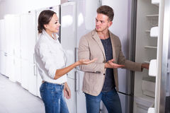 Young admiring couple choosing new refrigerator in hypermarket royalty free stock image