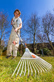 Spring raking. A young adolescent is forced to work in the garden and rakes the lawn on a sunny spring day royalty free stock photos