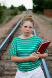 Young adolescent on tracks. A young adolescent girl with a book on railroad tracks going to school Royalty Free Stock Images