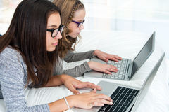 Young adolescents spending time on laptops at home. Royalty Free Stock Image