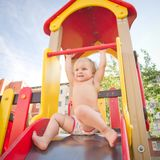 Young adorable baby sliding down baby slide Stock Photos