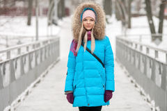 Young adorable blond woman wearing blue hooded coat strolling in snowy winter city park bridge. Nature cold season freshness conce Stock Photos