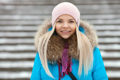 Young adorable blond woman wearing blue hooded coat strolling in snowy winter city park bridge. Nature cold season freshness conce Stock Image