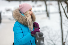 Young adorable blond woman wearing blue hooded coat strolling in snowy winter city park bridge. Nature cold season freshness conce Stock Images