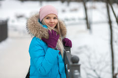 Young adorable blond woman wearing blue hooded coat strolling in snowy winter city park bridge. Nature cold season freshness conce Royalty Free Stock Photos