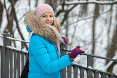 Young adorable blond woman wearing blue hooded coat strolling in snowy winter city park bridge. Nature cold season freshness conce Stock Photo