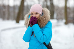 Young adorable blond woman wearing blue hooded coat strolling in snowy winter city park. Nature cold season freshness concept. Royalty Free Stock Photography