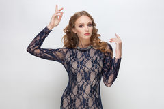 Young adorable blonde teen model in blue dress curly hairstyle doing an idea gesture posing on white studio background Royalty Free Stock Photos
