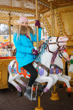Young adorable blonde woman enjoys the winter holidays on the city park carousel. Winter active city lifestyle concept. Stock Photos