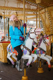 Young adorable blonde woman enjoys the winter holidays on the city park carousel. Winter active city lifestyle concept. Royalty Free Stock Images