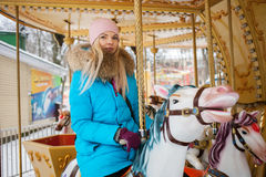 Young adorable blonde woman enjoys the winter holidays on the city park carousel. Winter active city lifestyle concept. Stock Image