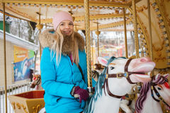 Young adorable blonde woman enjoys the winter holidays on the city park carousel. Winter active city lifestyle concept. Stock Photo