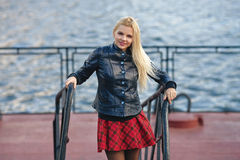 Young adorable blonde woman in red plaid skirt and leather jacket posing on river pier ladder in windy weather Royalty Free Stock Photography