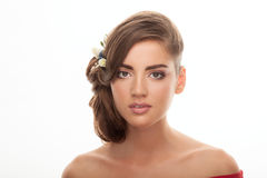 Young adorable brunette woman with cute makeup low bun hairstyle and flower headpiece with bare shoulders looking into camera with Stock Images