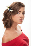 Young adorable brunette woman with cute makeup low bun hairstyle and flower headpiece in red shirt with bare shoulders looking int Royalty Free Stock Image