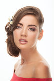 Young adorable brunette woman with low bun hairstyle, flower headpiece, and cute makeup posing with bare shoulders on white studio Royalty Free Stock Image