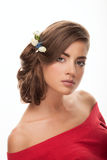 Young adorable brunette woman with low bun hairstyle, flower headpiece, and cute makeup posing with bare shoulders on white studio Royalty Free Stock Photos