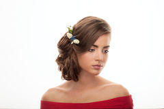 Young adorable brunette woman in red blouse with low bun hairstyle and flower headpiece showing trendy makeup Royalty Free Stock Images