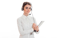 Young adorable business woman in uniform with headphones and microphone looking at the camera and make notes isolated on Royalty Free Stock Photography