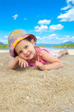 Young adorable girl girl at the beach. Adorable baby girl laying in the sand,at the beach Royalty Free Stock Images
