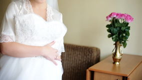 Young adorable happy bride touching her wedding dress and smile on camera. stock video