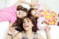 Young adorable hispanic sisters with mother lying Stock Image