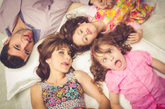 Young adorable hispanic sisters and parents lying Stock Image