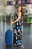 Young adorable lady. Posing at the airport standing next to a suitcase dressed in a long dress royalty free stock photo