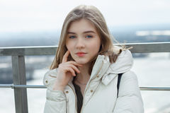 Young adorable student blonde teen girl having fun touching her chin on the observation deck with a view of cloudy spring sky, fro. Zen river, sunny windy stock photos