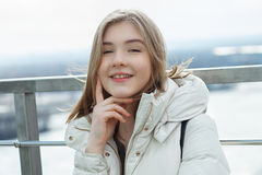 Young adorable student blonde teen girl having fun touching her chin on the observation deck with a view of cloudy spring sky, fro. Zen river, sunny windy royalty free stock photography
