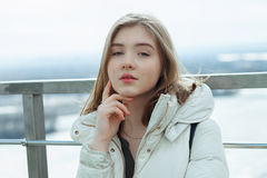 Young adorable student blonde teen girl having fun touching her chin on the observation deck with a view of cloudy spring sky, fro. Zen river, sunny windy stock photo