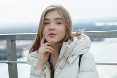 Young adorable student blonde teen girl having fun touching her chin on the observation deck with a view of cloudy spring sky, fro. Zen river, sunny windy stock photography