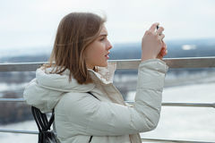 Young adorable student blonde teen girl takes photos with smartphone on the observation deck with a view of cloudy spring sky, fro. Zen river, sunny windy royalty free stock images