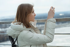 Young adorable student blonde teen girl takes photos with smartphone on the observation deck with a view of cloudy spring sky, fro. Zen river, sunny windy stock image