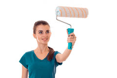 Young adorable woman with dark hair in uniforl makes renovations with paint roller in her hands isolated on white Stock Photos