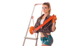 Young adorable woman with dark hair in uniforl makes renovations with tools in her hands isolated on white background Royalty Free Stock Image