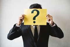 Young adult asian businessman holding yellow signboard paper with QUESTION MARK. Concept of business FAQ and questions royalty free stock photos