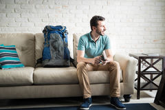 Ready to go to an expedition. Young adult with a backpack ready to go on a travel expedition and waiting for his friends at home Royalty Free Stock Image