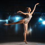 Young adult ballerina posing on stage in theater Royalty Free Stock Photography