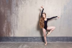 Young adult ballet dancer posing in studio. Contemporary dance p. Erformer. Indoor shot, gray wall stock image