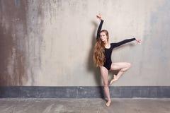 Young adult ballet dancer posing in studio. Contemporary dance p. Erformer. Indoor shot, gray wall stock image