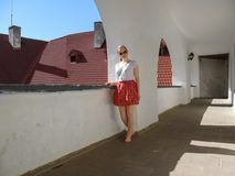 Young adult barefoot girl stands in the old corridor in the Castle Palanok