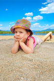 Young adult at the beach. Cute girl laying in the sand with serious face expresion Royalty Free Stock Photo