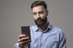 Young adult bearded happy businessman reading message or taking picture on mobile phone. Against gray studio background Royalty Free Stock Photo